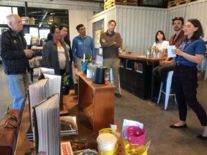 Woman speaks to audience in coffee roastery