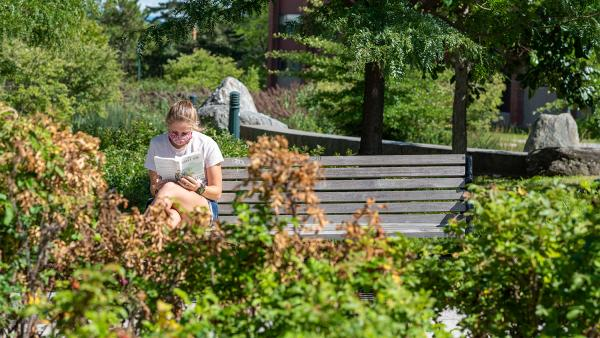 A young woman wearing a face mask reads on a park bench