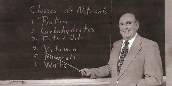 man teaching in front of a blackboard