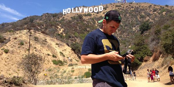 """Braden Duemmler adjusts a camera below the """"Hollywood' sign in Los Angeles"""