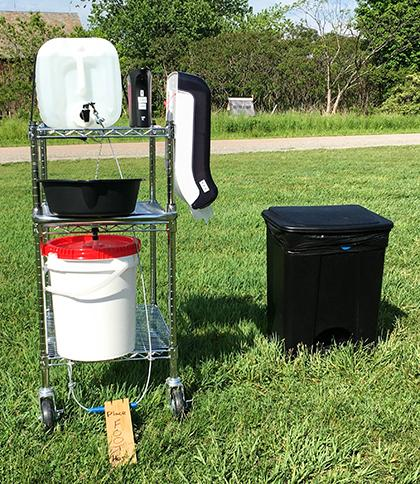 handwashing station on a rolling cart with water, paper towl and soap dispensers, catch basin and bucket for used water, and garbage can