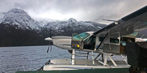 Sea plane docked beside snow-capped mountains in Alaska