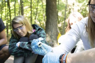 Watershed Educator interns with safety glasses in woods