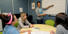 Students receiving group tutoring, at whiteboard