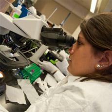 med student using microscope