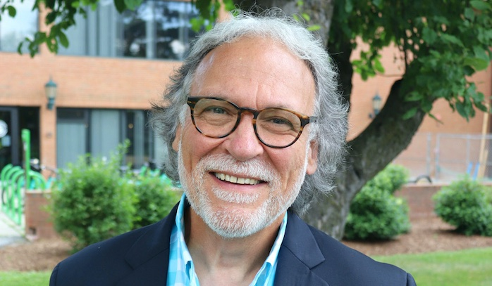 Michael Giangreco profile photo: an older white man with short white hair, glasses, and full white beard and mustache stands smiling proudly in front of a red brick building and a lush green tree.