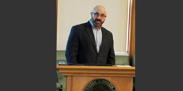 Chris Vaccaro speaking at a podium, dark beard, wearing glasses