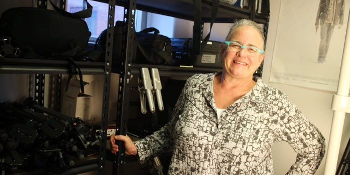 Deb Elliz, next to film equipment, wearing glasses, smiling into camera