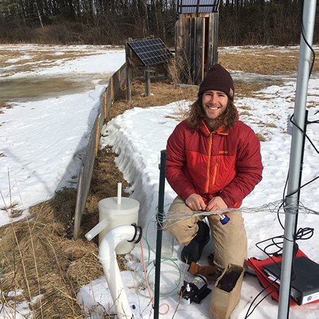 Graduate student Cam Twombly in an agricultural field with monitoring infrastructure