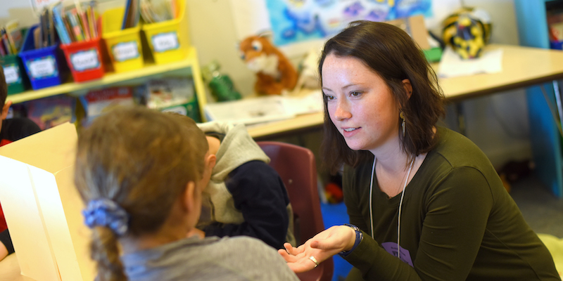 Special Education Teacher engaging with a student in a school classroom