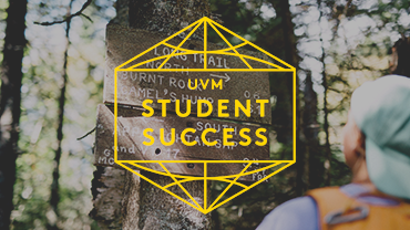 a student looking up at a trail sign in the woods with the student success badge overlayed