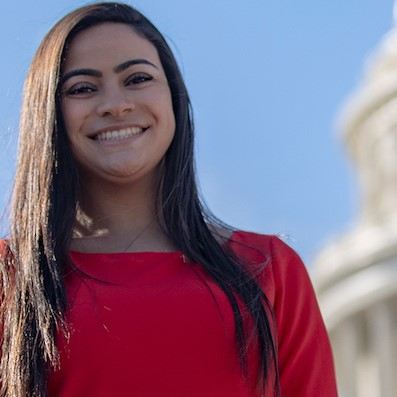 Student smiling in front of the Capital Building in D.C.