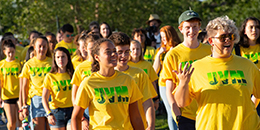 group of students wearing green and gold tshirts at convocation