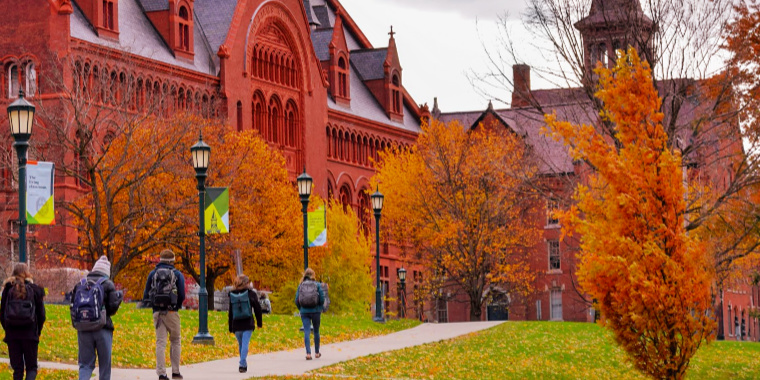 Students walking away on sidewalk next to green lamppost.  Fall trees in foliage in the back ground.