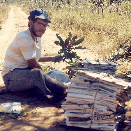 A young Dr. Hill sits by a dirt road, pressing stacks of specimens in newspapers