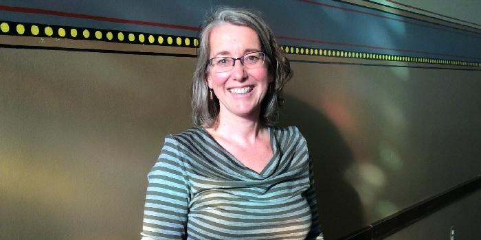 Libby Miles, smiling at camera, wearing glasses, shoulder length grey hair
