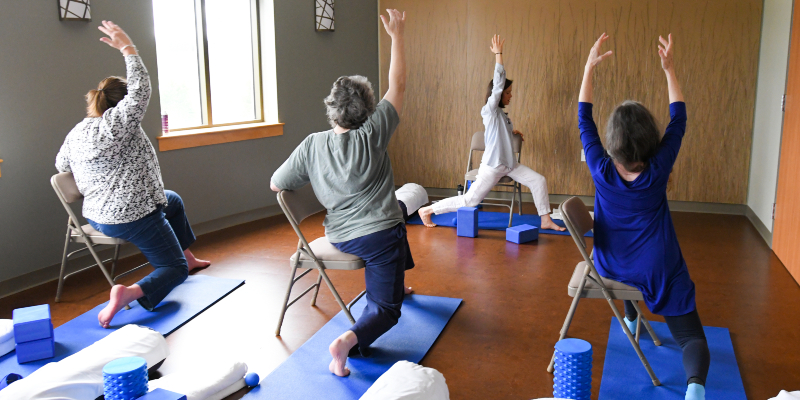 Three people with arms raised in a yoga pose with yoga instructor demonstrating