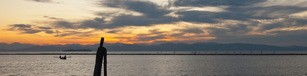 A sunset photo of Lake Champlain with the UVM sailing team out on the horizon.