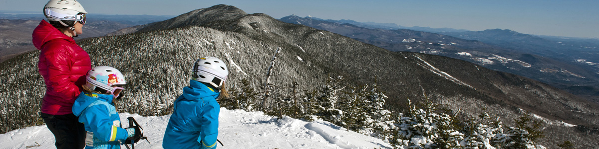 Three skiers atop mountain summit