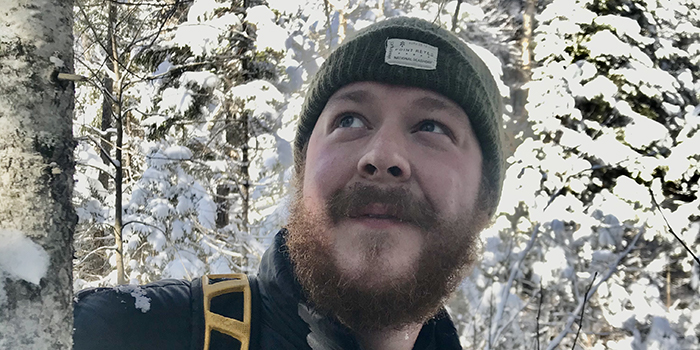 image description: man with beard and hat among snowy trees