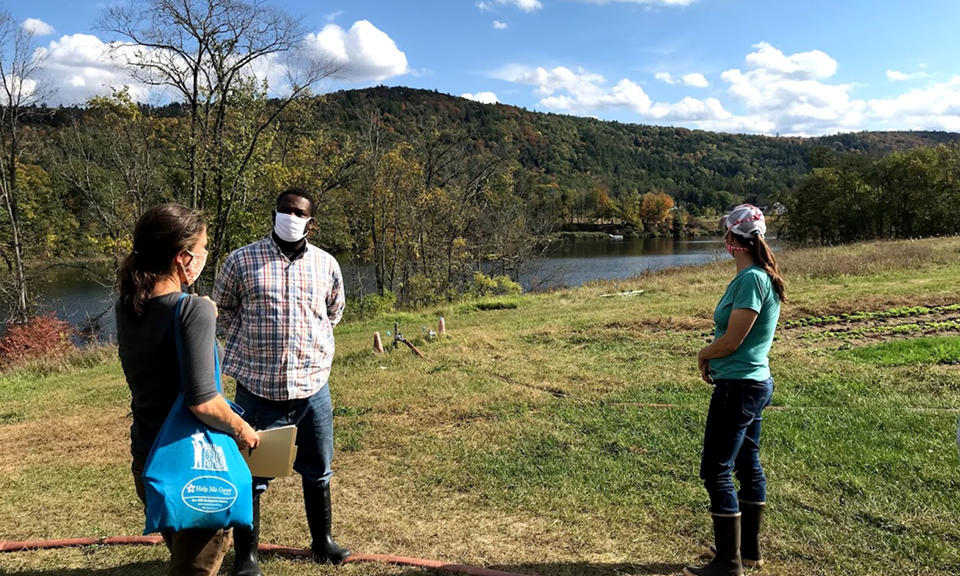 image description: three masked people in a green field with a waterway nearby