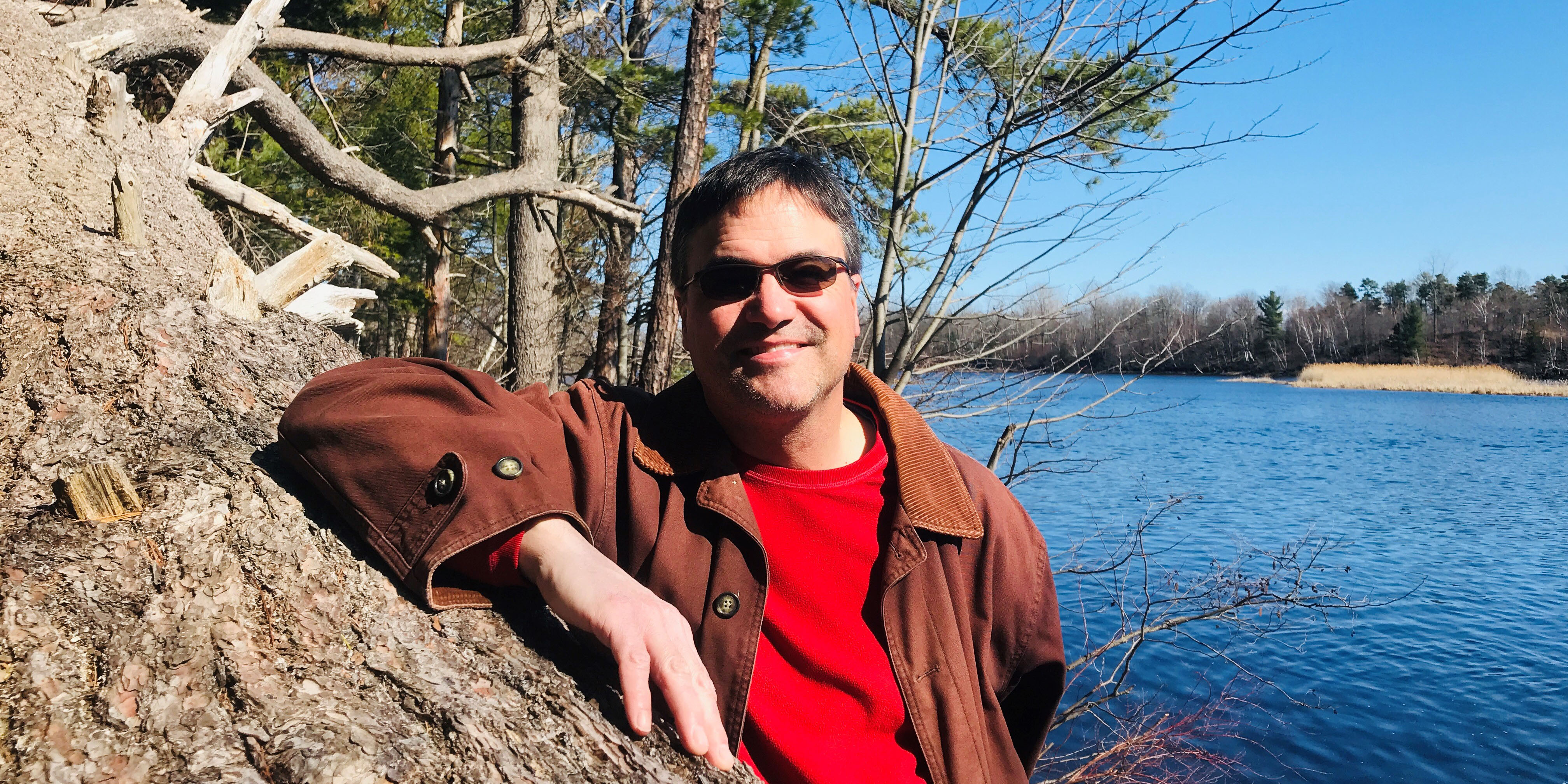 image description: smiling man in red shirt and brown jacket standing near blue water on a sunny day