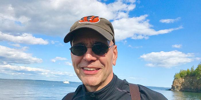 Todd McGowan, wearing baseball cap and sunglasses, smiling at camera