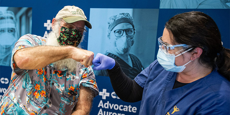 Dr. Akbarnia fist bumps in celebration with former patient as he receives second vaccine from her.