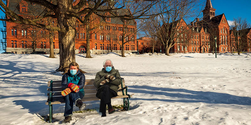 Jen Ellis poses like and with Bernie Sanders on a bench at UVM.
