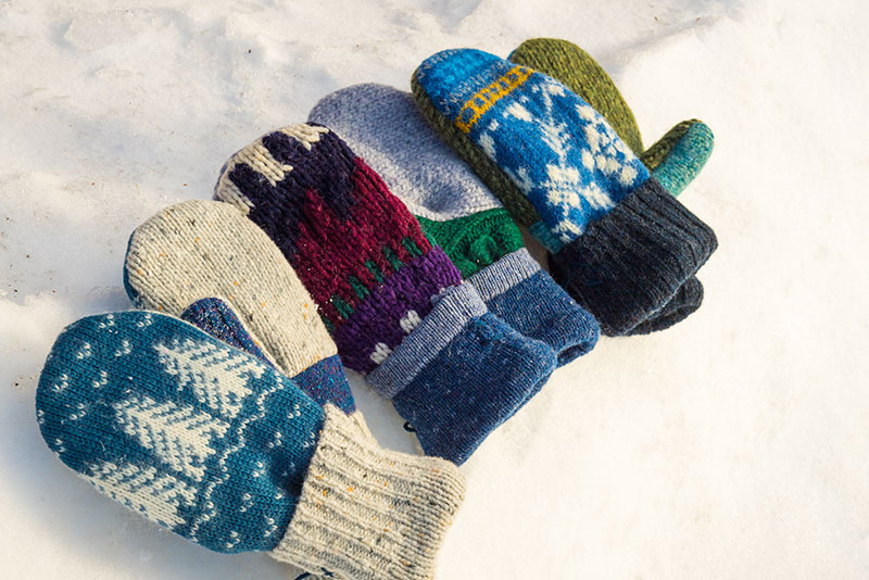 Mittens made by Jen Ellis rest on packed snow.