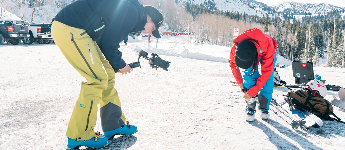 Hilary Byrne '11 films skier suiting up on snowy mountain