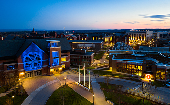 UVM Central Campus lit up in blue light at night, seen from a drone