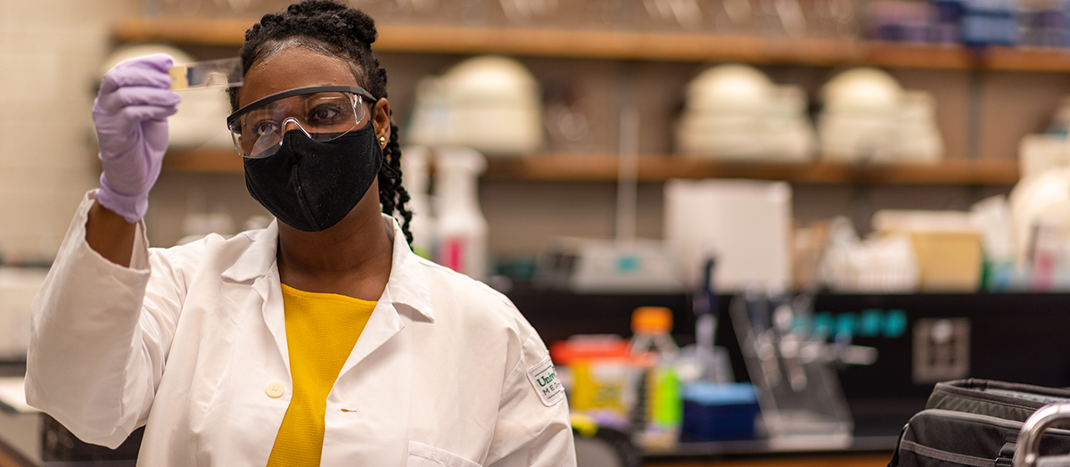 Medical laboratory student Christol Long holds a test tube to the light in a lab, wearing lab coat and mask