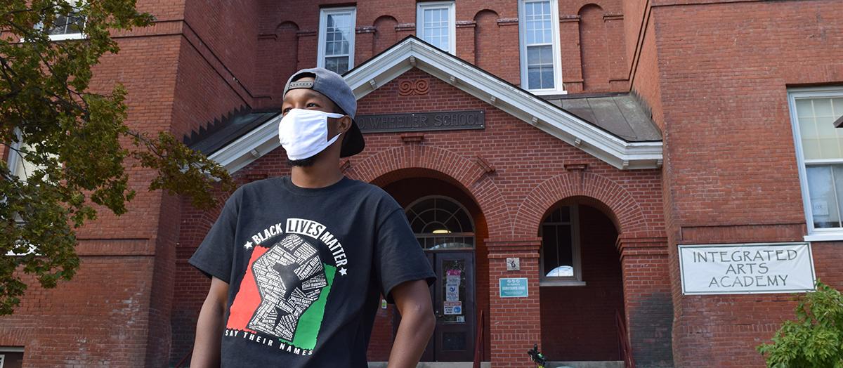 Aden Haji '19 stands in front of Integrated Arts Academy building in Burlington