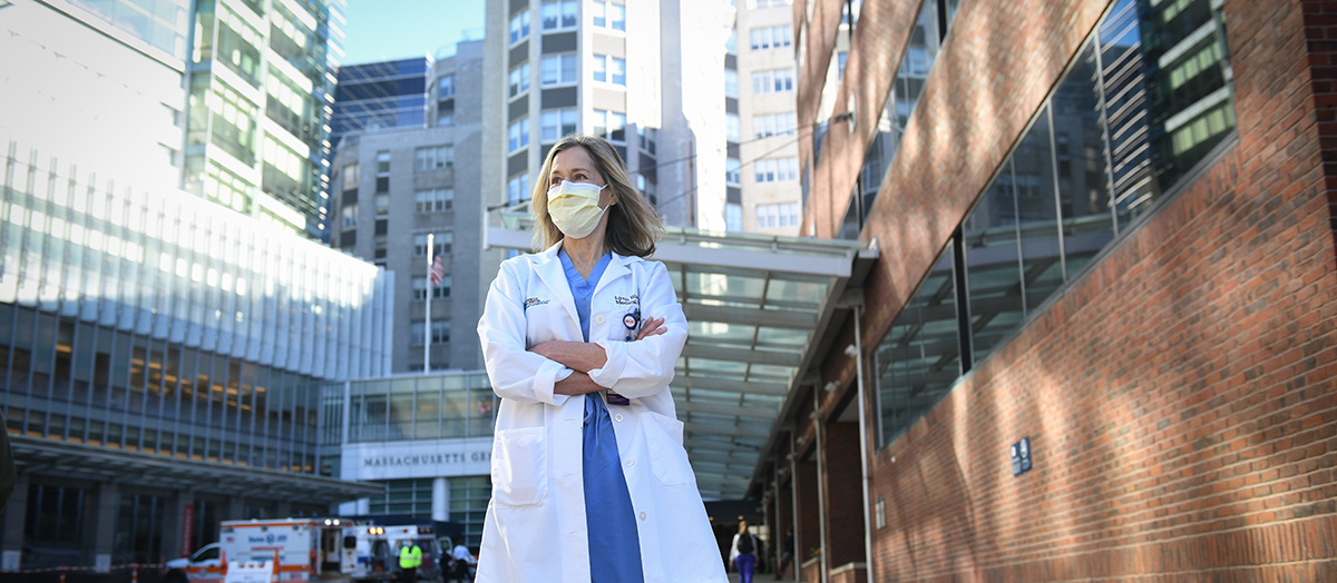 Dr. Lynn Black stands in lab coat and mask in front of Mass General Hospital