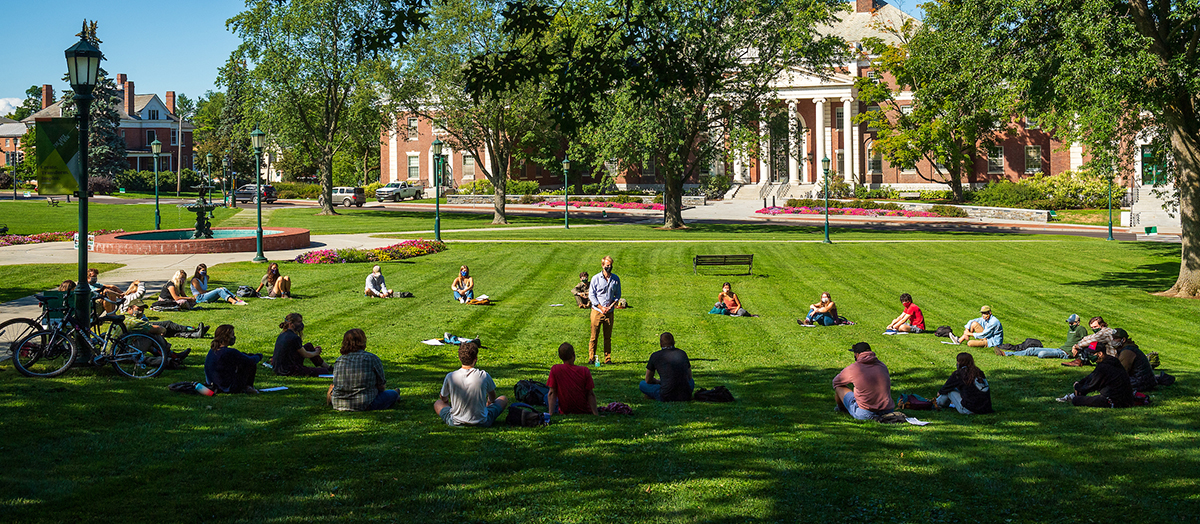 Classmates sit in a socially distanced circle on the UVM Green in early fall, surrounding their instructor, center