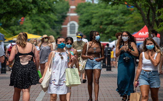 A crowd of masked people walk on Burlington's Church Street in summertime
