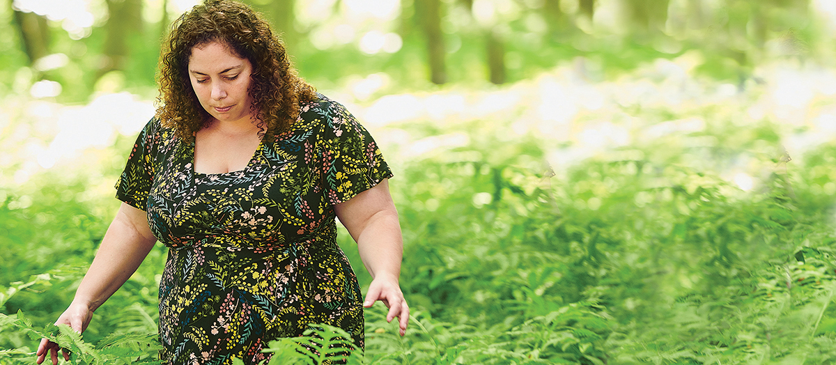 UVM alumna Melody Walker walks through forest