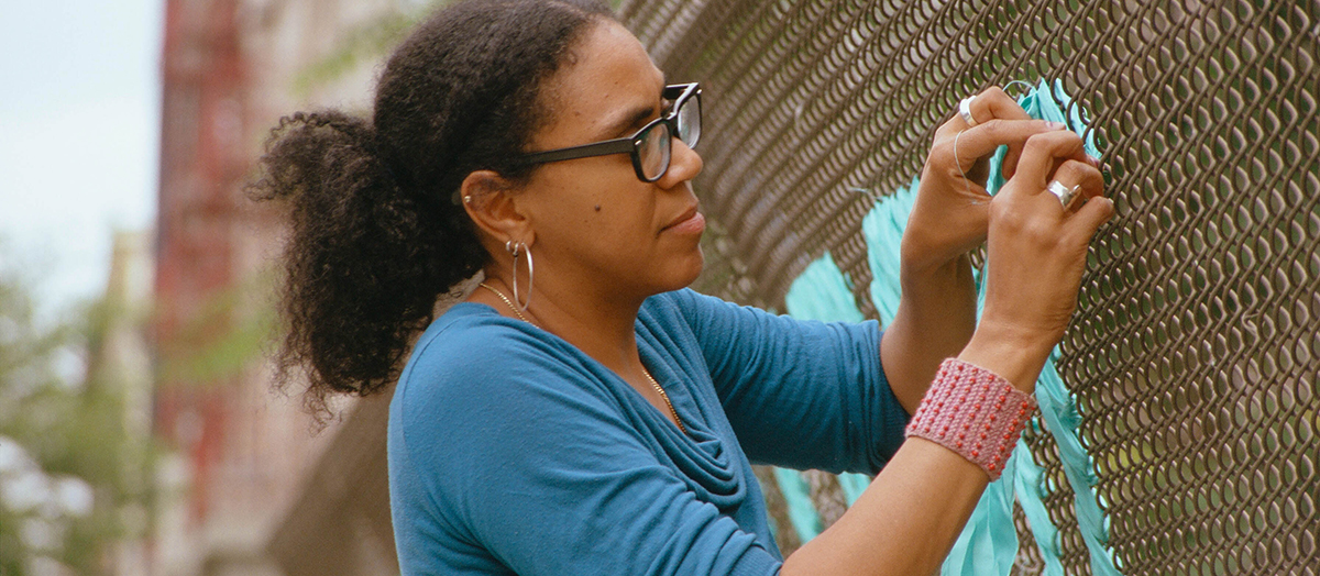 Artist Mildred Beltré weaves fabric into chainlink fence in Brooklyn