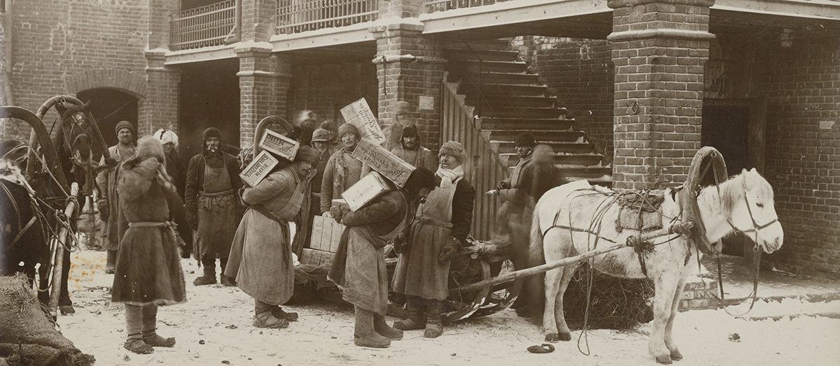 During Russian famine of 1920s, people carry crates of food