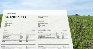 Balance sheet with farm equipment in field