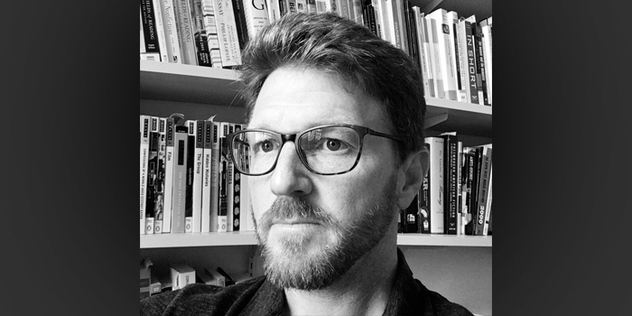 Greg Bottoms, with beard and glasses looking off camera, image is black and white