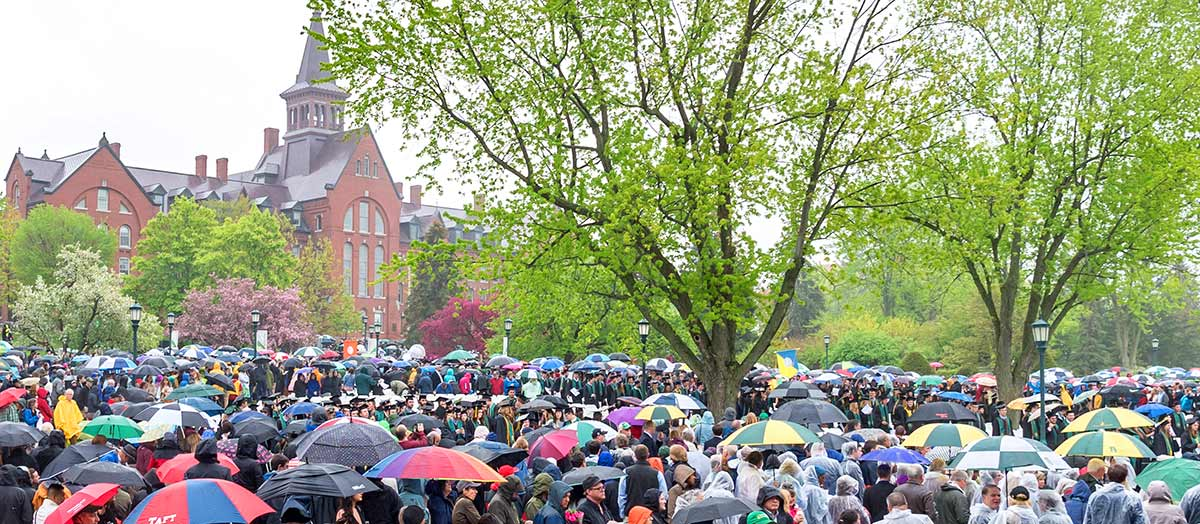 A sea of umbrellas on the UVM green in front of Old Mill for Commencement 2018