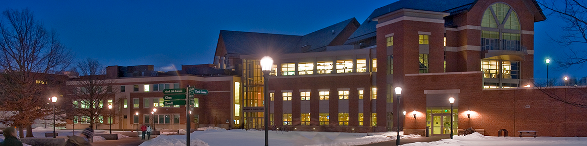 Dudley H Davis Center at Night on a Snowy Night with Student Walking