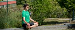 Student meditating on campus green