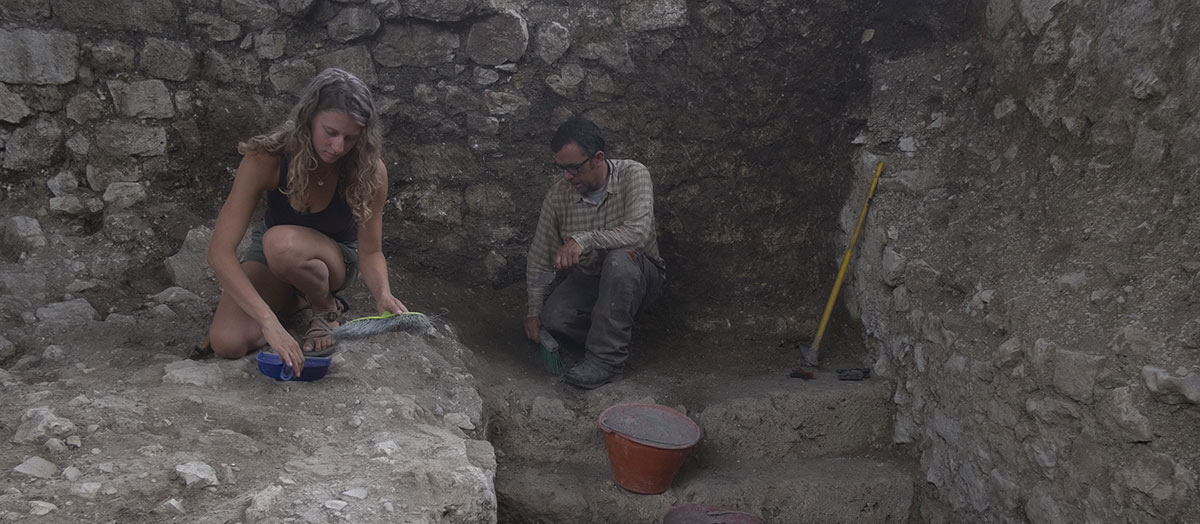 A student and professor kneel in an archaeological dig site surrounded by rock walls, using tools