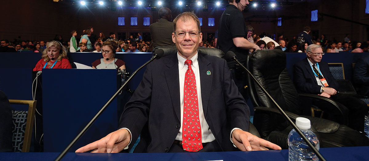 UVM Professor Jacques Bailly behind the pronouncer desk at the Scripps National Spelling Bee