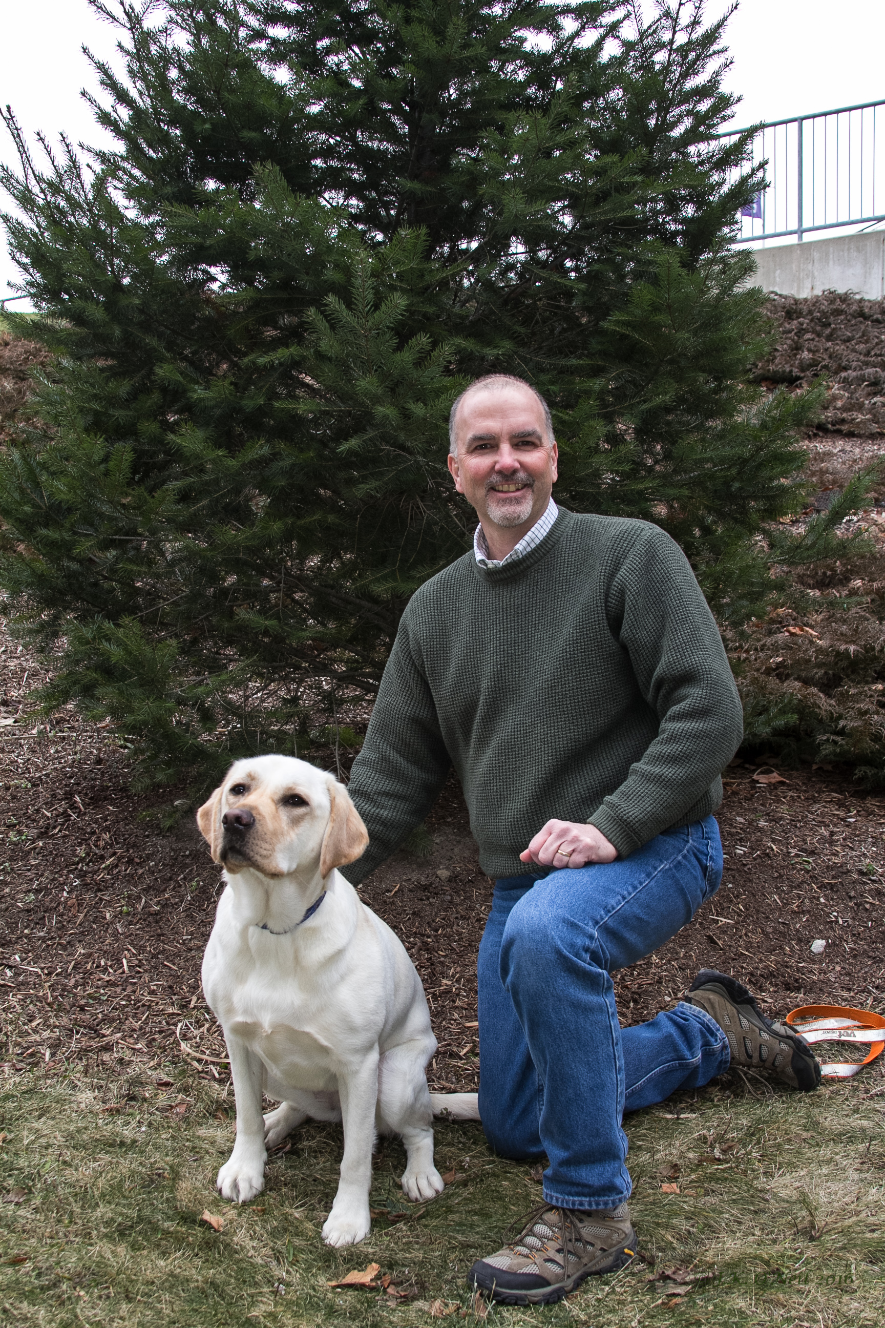 Dr. Townson the department chair kneeling with his yellow lab Zoe