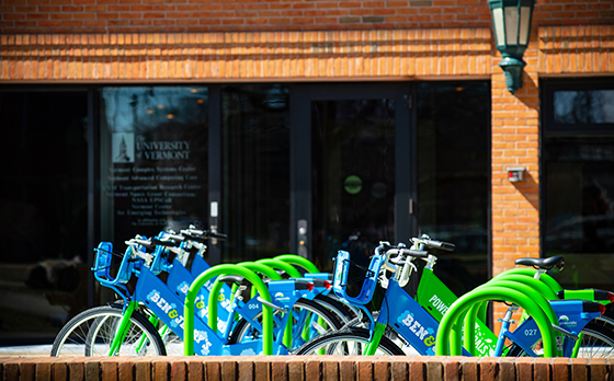 Bikes sit in a rack in front of a UVM building.
