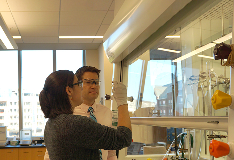 Photo of Prof. Rory Waterman with student in the lab, analyzing chemical reactions.